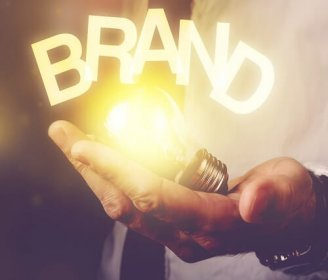 Brand idea concept with businessman holding light bulb, retro toned image, selective focus.