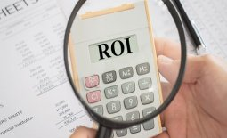 ROI text on calculator with magnifying glass. Concept of return on investment, analysis finance.